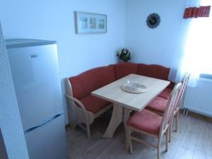 Eckbank mit zwei Stühlen und Gefrierkombination in Wohnung zwei