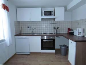 neue Küchenzeile mit Geschirrspülmaschine, Mikrowelle, Backofen mit vier Herdplatten, Kaffeemaschine, Wasserkocher und Toaster
