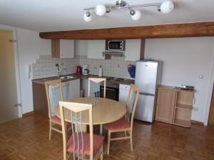 Wohnküche mit Geschirrspülmaschine, Backofen mit vier Herdplatten, Mikrowelle, Gefrierkombination, Kaffeemaschine, Toaster, Wasserkocher, Esstisch mit vier Stühlen