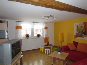 Wohnzimmer mit Schlafsofa, Fernseher und Kinderspielecke